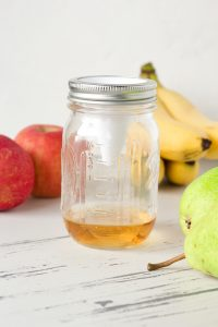mason jar with apple cider vinegar and Culinesco fruity fly funnel with fruit in the background