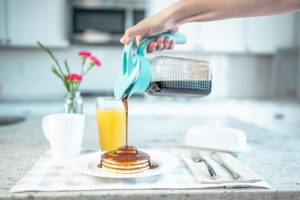 maple flavored syrup being poured from a mason jar with an Ergo Spout