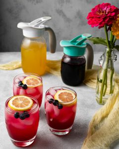 Blue berry lemonade in glasses with 2 Ergo Spouts on mason jars in the background
