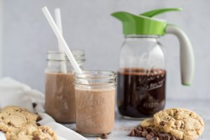 Mason jar with chocolate syrup and an Ergo Spout with two glasses of chocolate milk on the side - side view