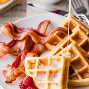 Buttermilk syrup being poured on waffles with bacon on the side