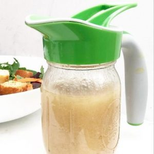 Champagne Salad Dressing on a mason jar with a green Ergo Spout