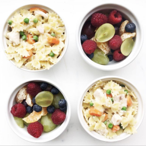 Two bowls with Healthier Alfredo Sauce over pasta and peas plus two bowls of fruit