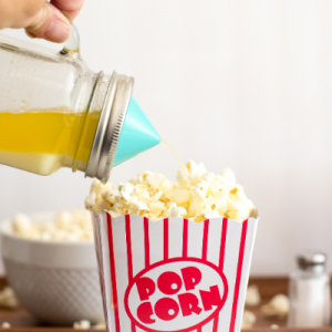 Melted butter in a mason jar with an Ergo Spout Mini dispensing the butter onto popcorn