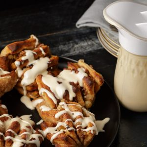 Apple cinnamon roles with caramel icing drizzles over them and a mason jar with an ergo spout