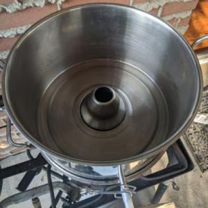 The middle section of a steam juicer with a hole in the middle for the steam