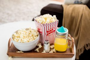 TV tray by sofa with bowl of popcorn and melted butter in mason jar with Ergo Spout Mini on top