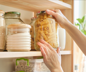 Woman reaching for pasta in a glass jar on a shelf