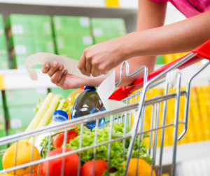 Woman holding a grocery receipt by a shopping cart
